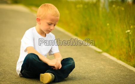 little thoughtful boy child outdoor portrait