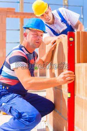 dos artesanos inspeccionan las paredes en