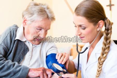 la enfermera medir la presion arterial