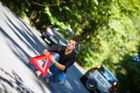 apuesto joven con su coche averiado