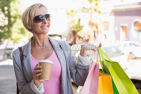 feliz mujer madura caminando con compras
