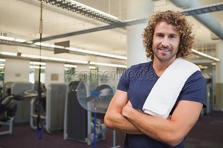sonriente entrenador guapo con los brazos