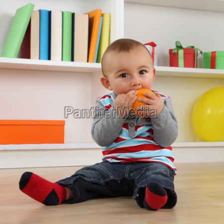 el pequenyo bebe come una fruta