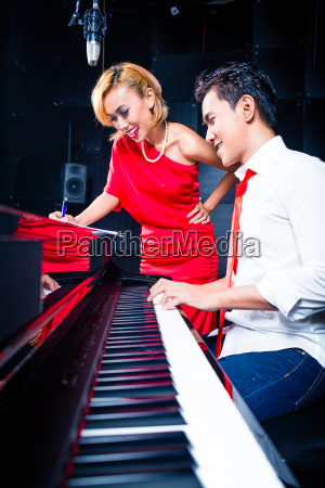 asian professional musician recording song in