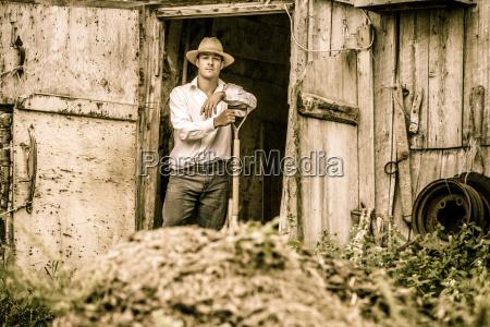 farmer shoveling el estiercol de caballo