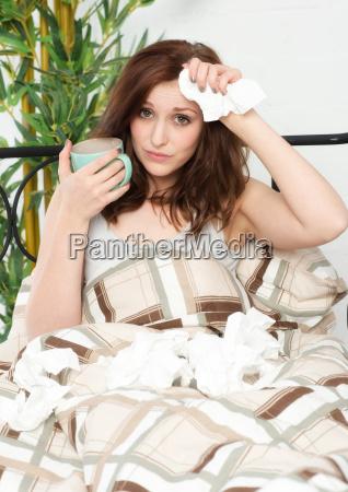 mujer joven acostada enferma en la