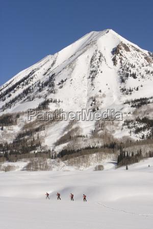 cuatro esquiadores alpinos recorrido en la