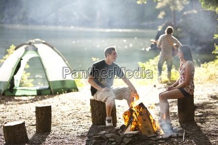 los adultos jovenes de camping sentarse