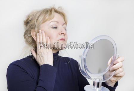 mujer mayor mira en el espejo