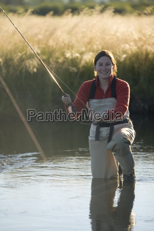 young woman fly fishing in a