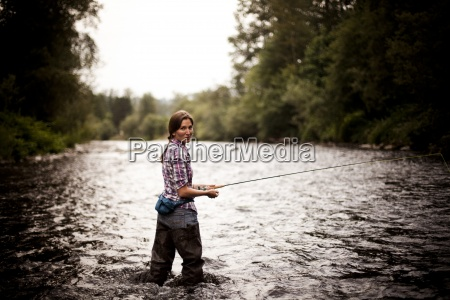 a young woman fly fishes in