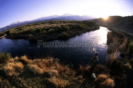 a man fly fishing at sunset