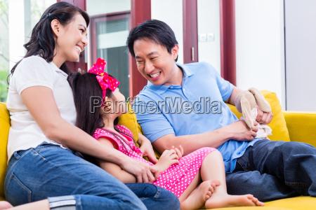 familia china jugando con la hija