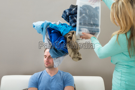 mujer tirando ropa sobre el marido