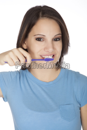 mujer caucasica cepillarse los dientes