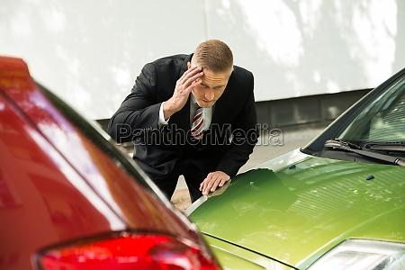 conductor estresado mirando al coche despues