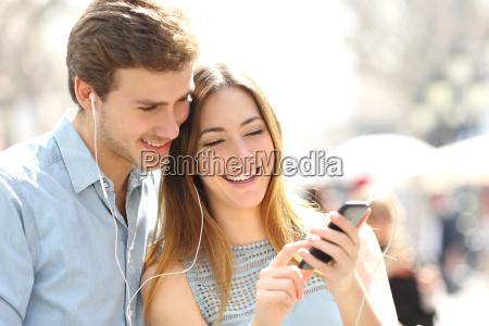 pareja compartir musica desde un telefono