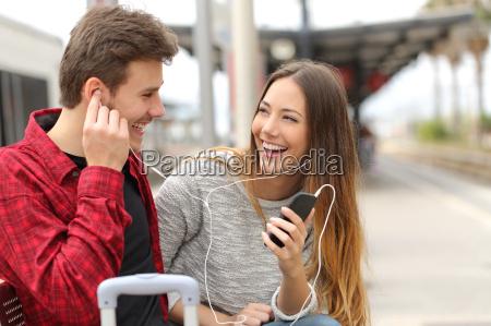 feliz pareja de viajeros compartiendo musica