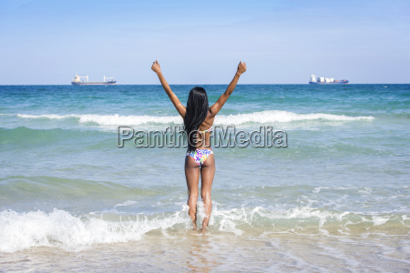 woman at the beach hands up