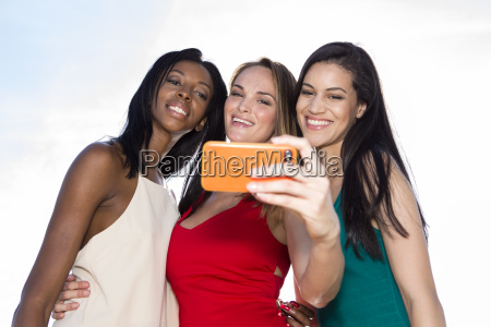 portrait of three women taking selfies
