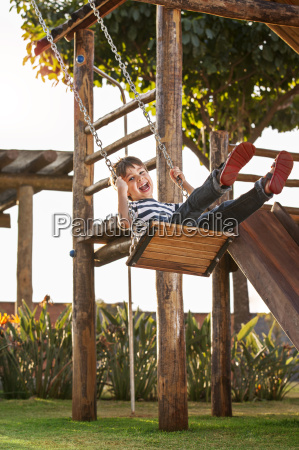cute boy playing on swing having