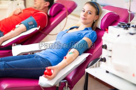 mujer joven dando sangre en un