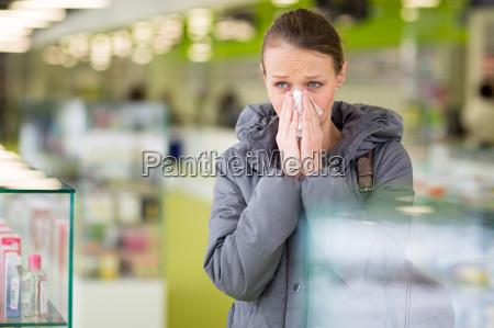 mujer joven que sopla su nariz