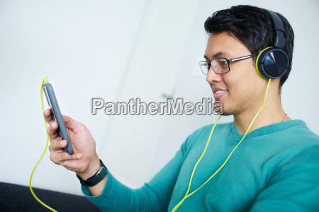 hombre chino con los auriculares verdes