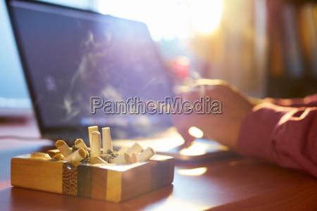 hombre usando computadora portatil y fumando