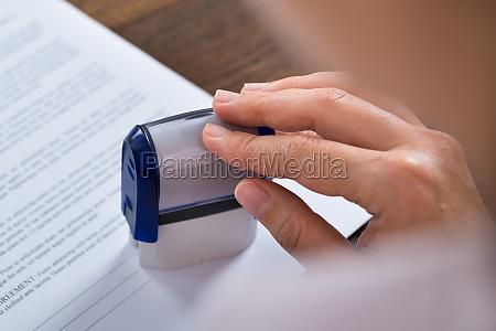 persona manos con stamper y documento