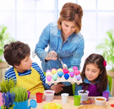familia feliz pintar huevos de pascua