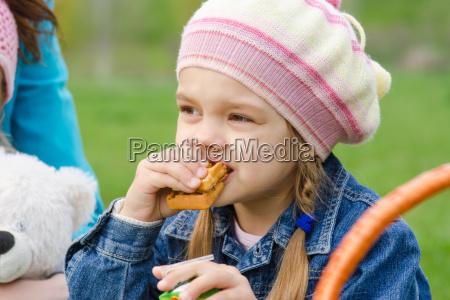 chica comiendo pastel en un picnic