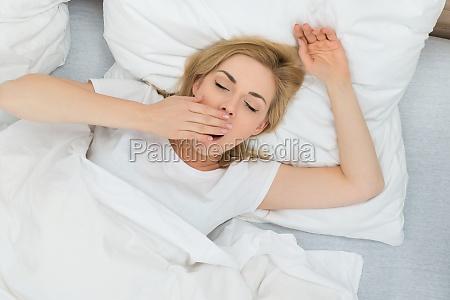 mujer de bostezo en el dormitorio