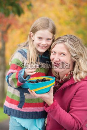 madre e hija compartiendo moras