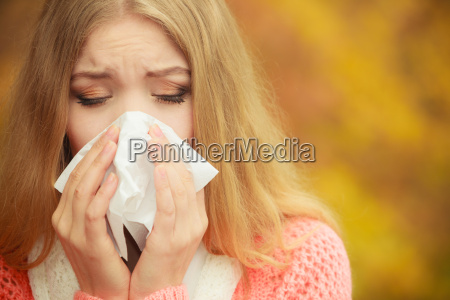 enferma enferma en autumn park estornudando