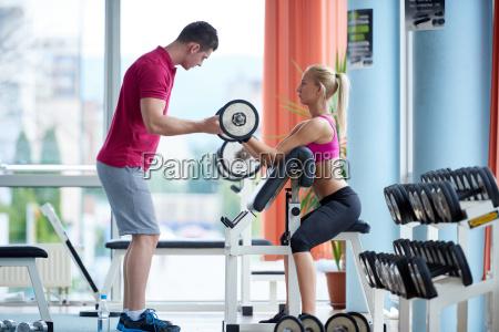 joven mujer deportiva con entrenador ejercicio