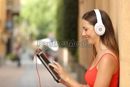chica hojeando una tableta y escuchando