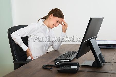 empresaria sufriendo de dolor de espalda