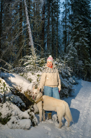 woman with dog in winter forest