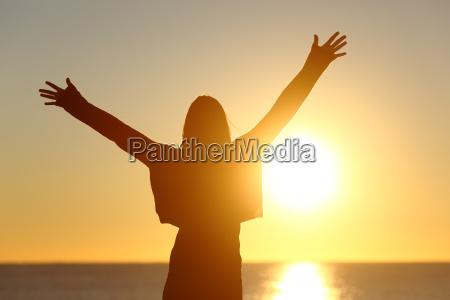 mujer libre levantando brazos viendo el