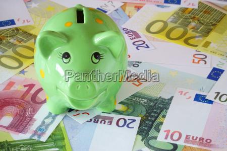 alcancia verde y billetes de banco