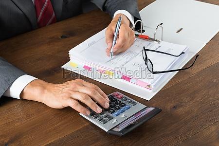 contable verificando factura con calculadora