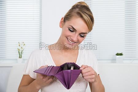 mujer mirando dinero en monedero