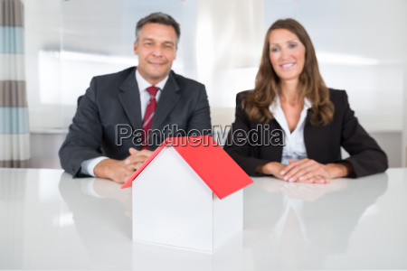 businesspeople looking at house model on