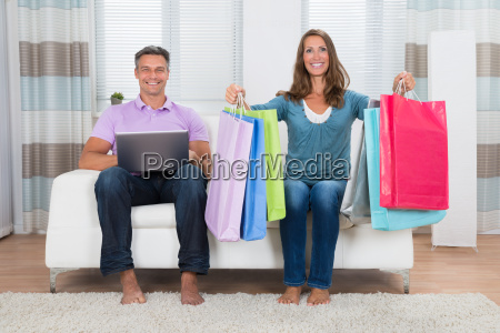 couple with shopping bags and laptop
