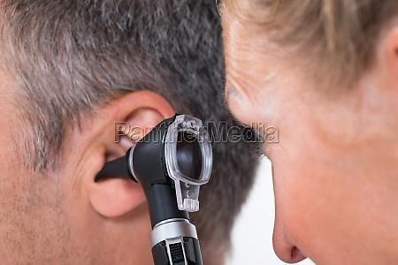 medico que examina la oreja del