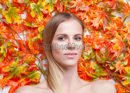 beautiful young woman lying on leafs