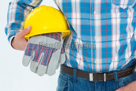 construction worker holding hard hat and