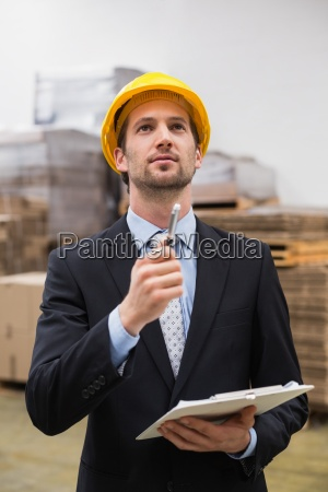 warehouse manager wearing hard hat checking