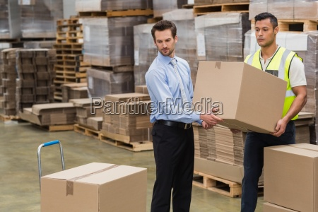 warehouse worker and manager carrying a